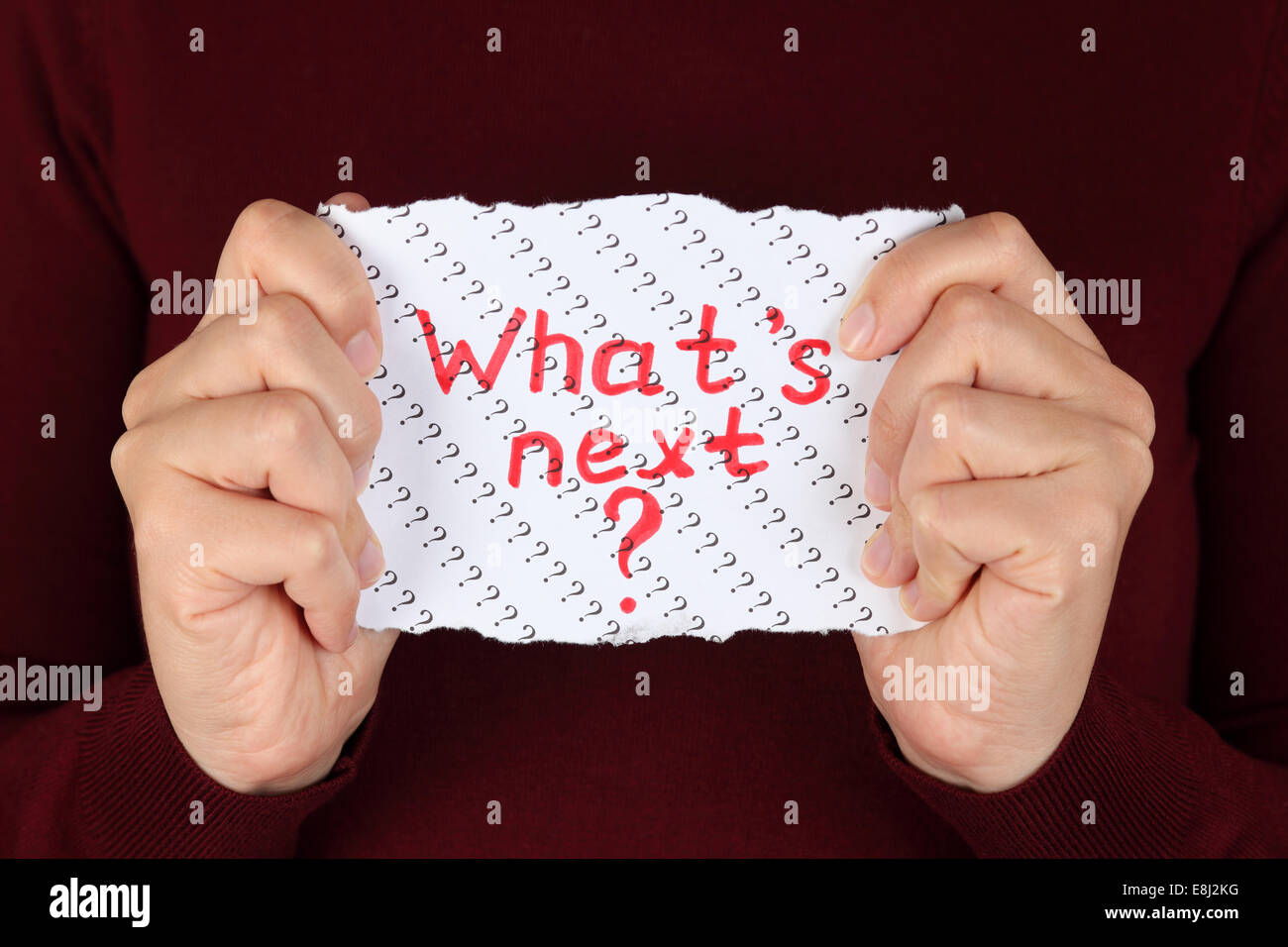 Piece of paper with red words 'What's next?' in the woman's hands. - Stock Image