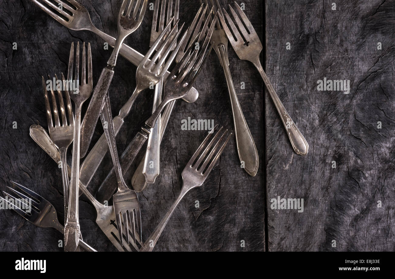 An array of antique forks scattered on a rustic gray wood surface. - Stock Image