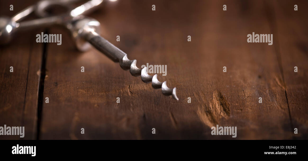 Antique corkscrew on rustic wood surface. - Stock Image