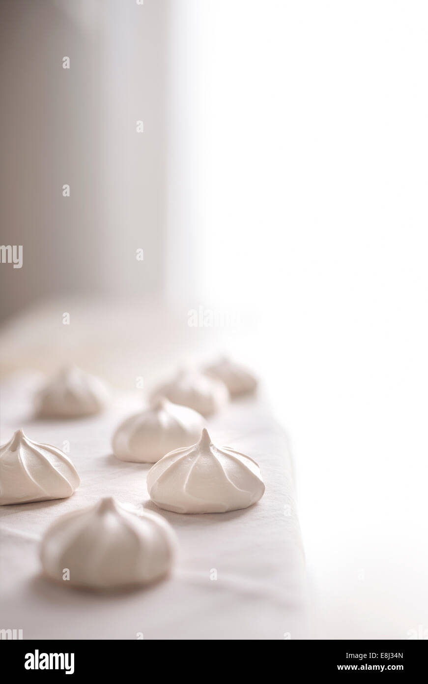 Vanilla meringue cookies on white linen with bright light background. - Stock Image