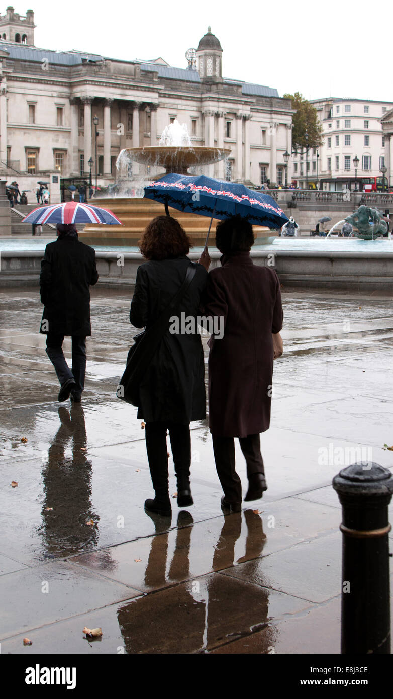 People with umbrellas in wet weather, Trafalgar Square, London, UK - Stock Image