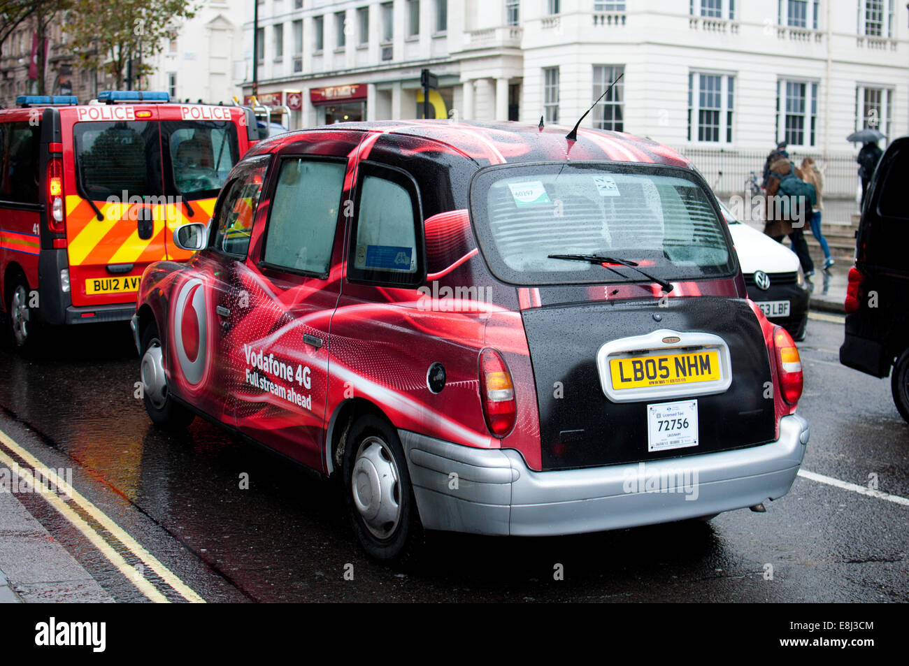 London taxi with Vodafone 4G advertisement, in wet weather, London, UK - Stock Image