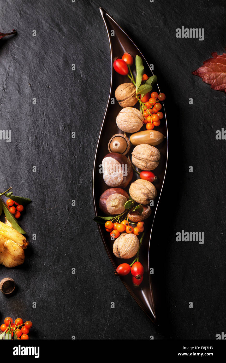Decorative ceramic plate with nuts, berries and mushrooms over black background. - Stock Image