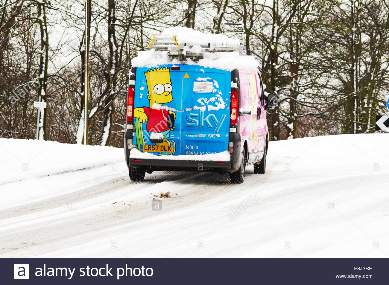 Sky television media van with bart simpson painted on the back door approaching a roundabout in the snow - Stock Image