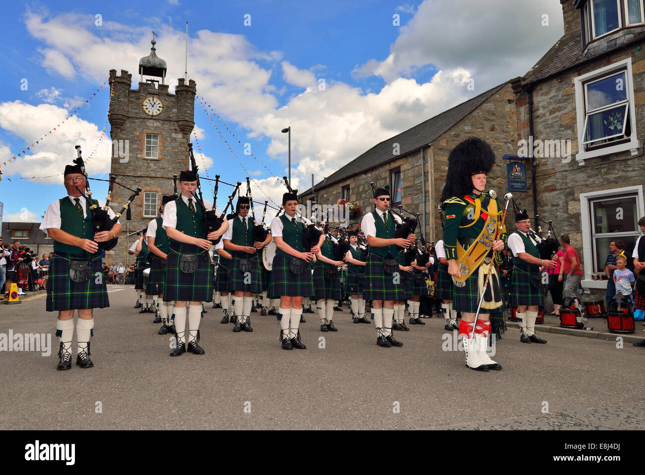 Pipe major leading a pipe band, stationary in front of the clock tower in the town centre, Dufftown, Moray, Highlands, - Stock Image