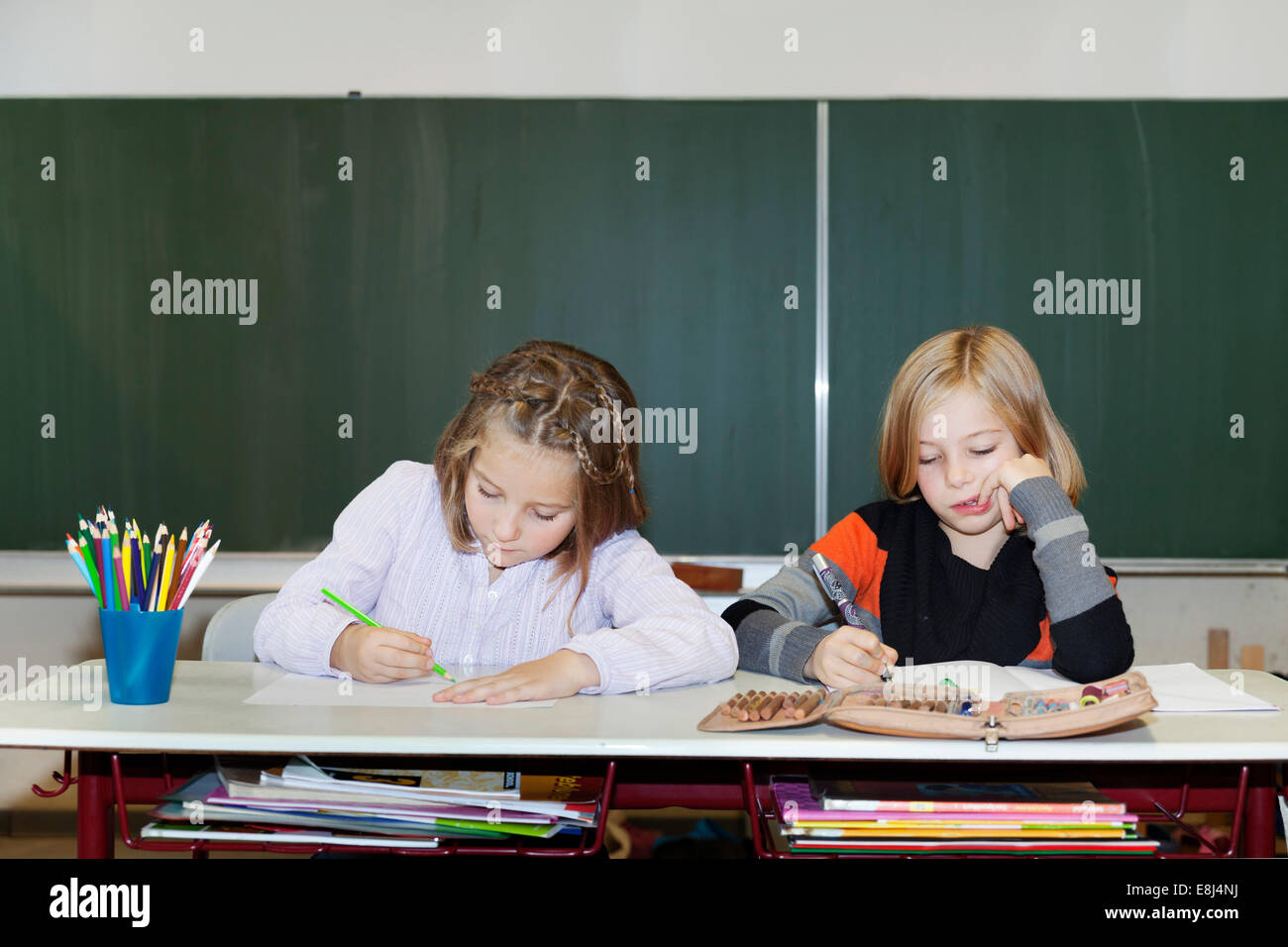 Two schoolgirls, 7 and 9 years, at school - Stock Image