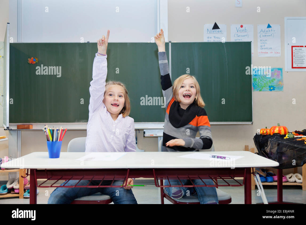 Two schoolgirls, 7 and 9 years, putting up their hands in class - Stock Image
