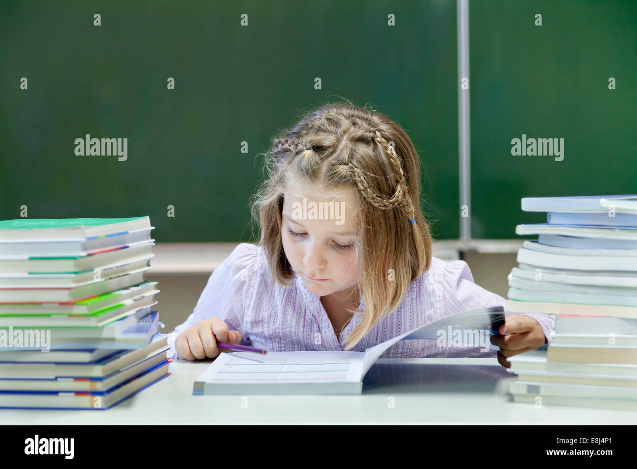 Schoolgirl, 7 years, reading a book whilst sitting between two stacks of books, in front of a blackboard - Stock Image
