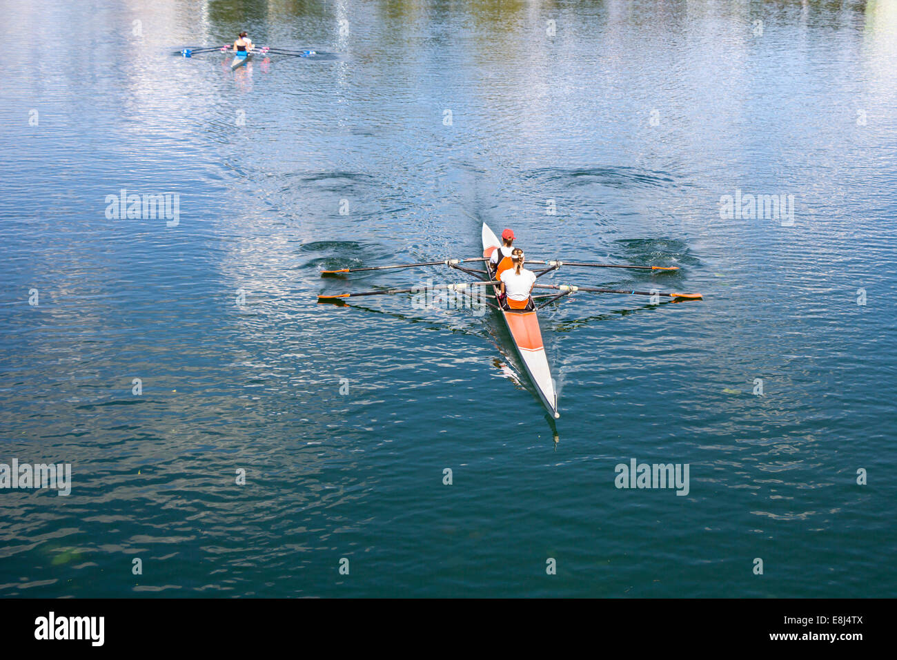 Two Women Rower in a boat, rowing on the tranquil lake Stock Photo
