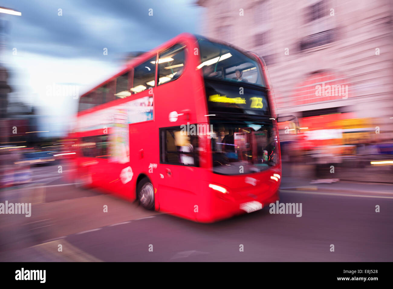 Red double decker bus, motion blur, Piccadilly Circus, London, England, United Kingdom - Stock Image