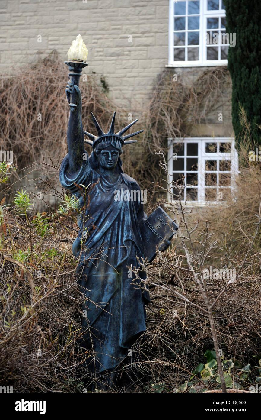 a statue of liberty garden ornament in an overgrown english garden uk - Liberty Garden