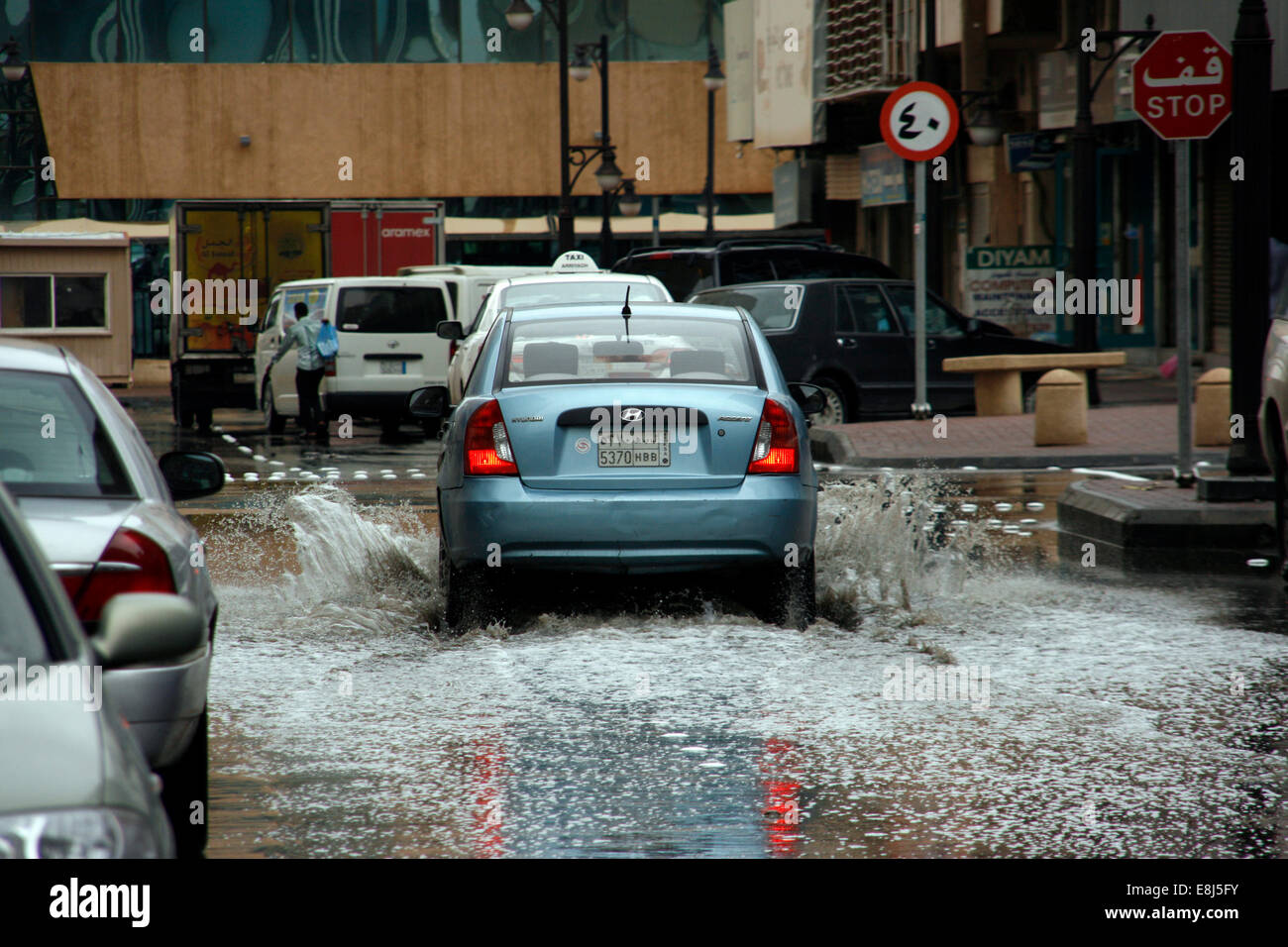 A car drives through the built-up rain water in the streets of Riyadh, Saudi Arabia - Stock Image