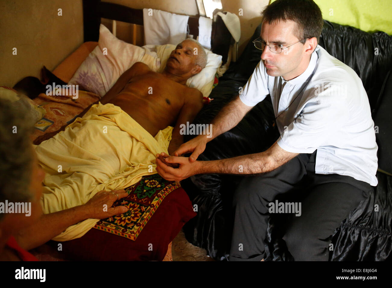 French priest Etienne Kern visiting a dying parishioner in Alagados favela - Stock Image