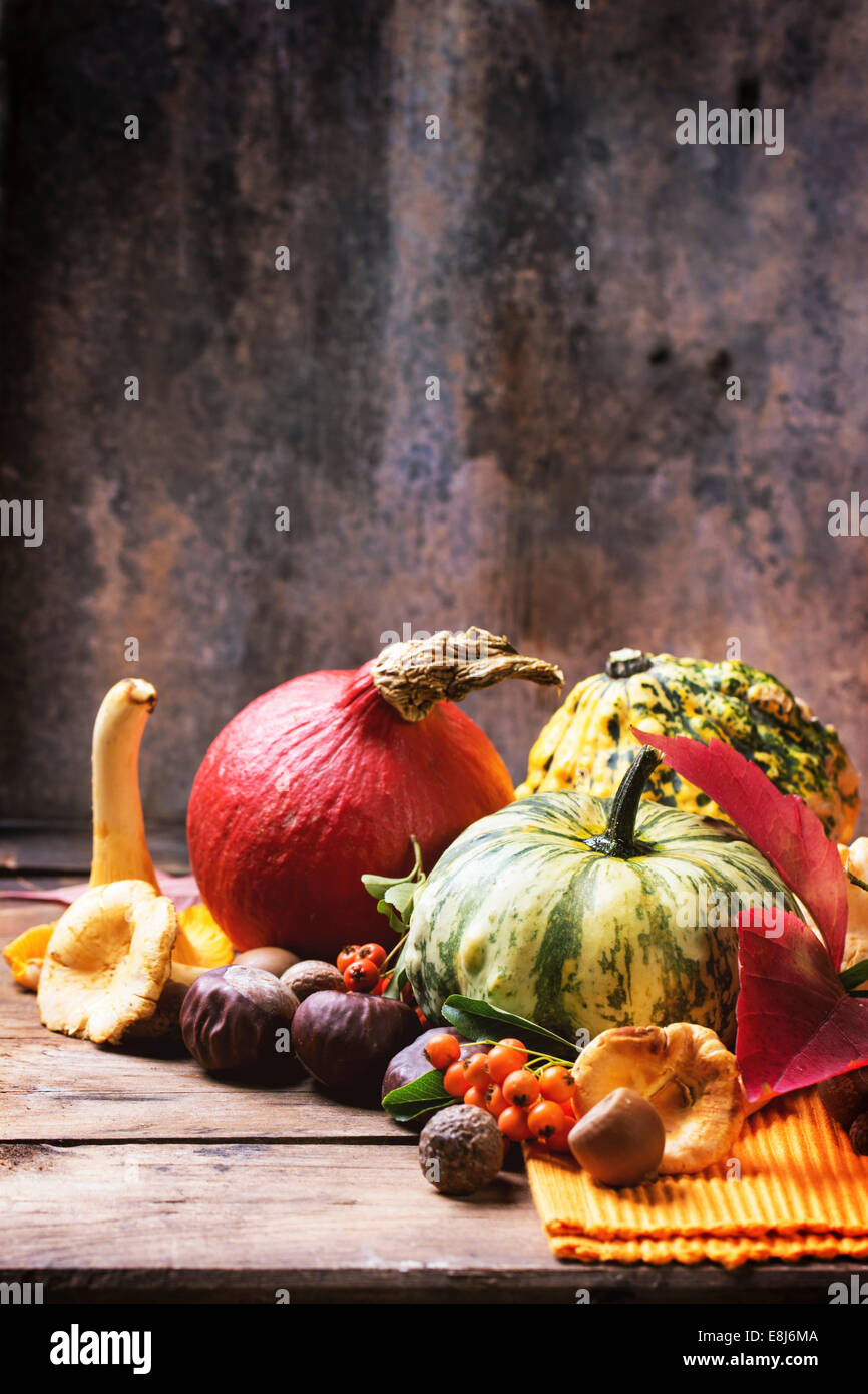 Pumpkins, nuts, berries and mushrooms chanterelle over old wooden table. - Stock Image