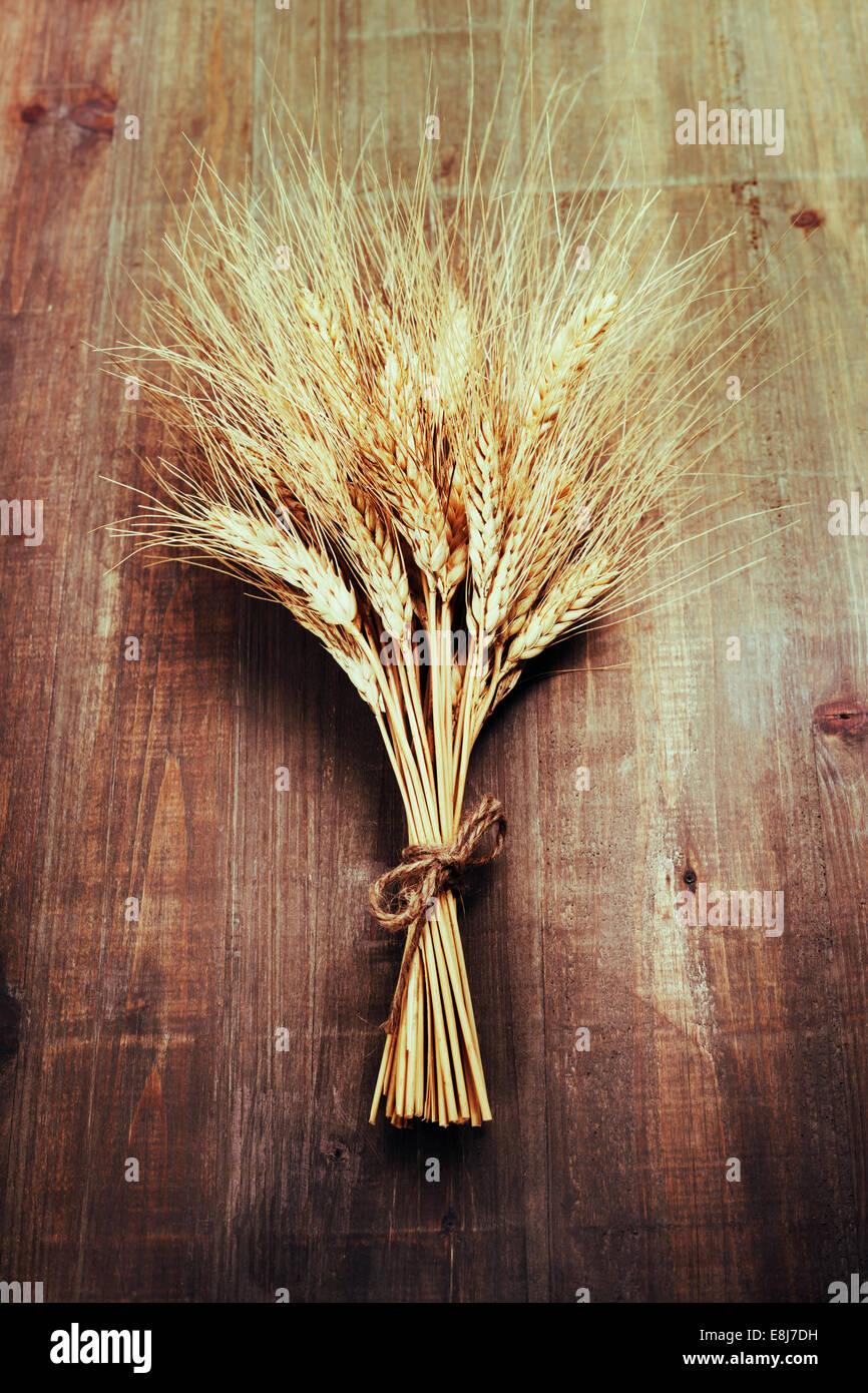 Wheat ears on wooden background - Stock Image