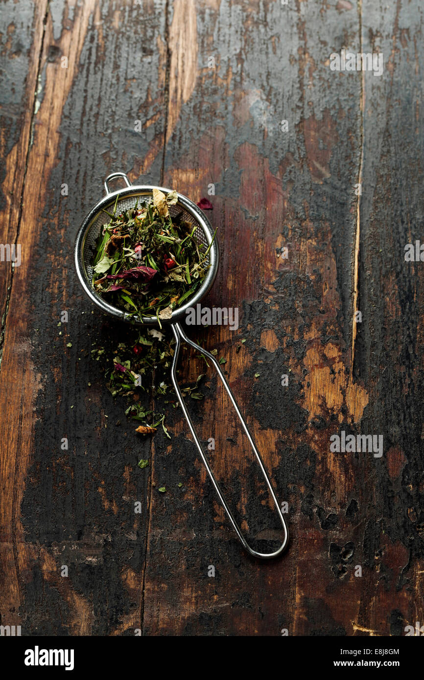 Tea stainer with aromatic herbal tea on wooden table background - Stock Image