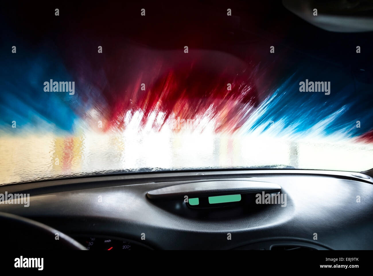 Motion blurred picture of car wash from inside a car during the wash. - Stock Image