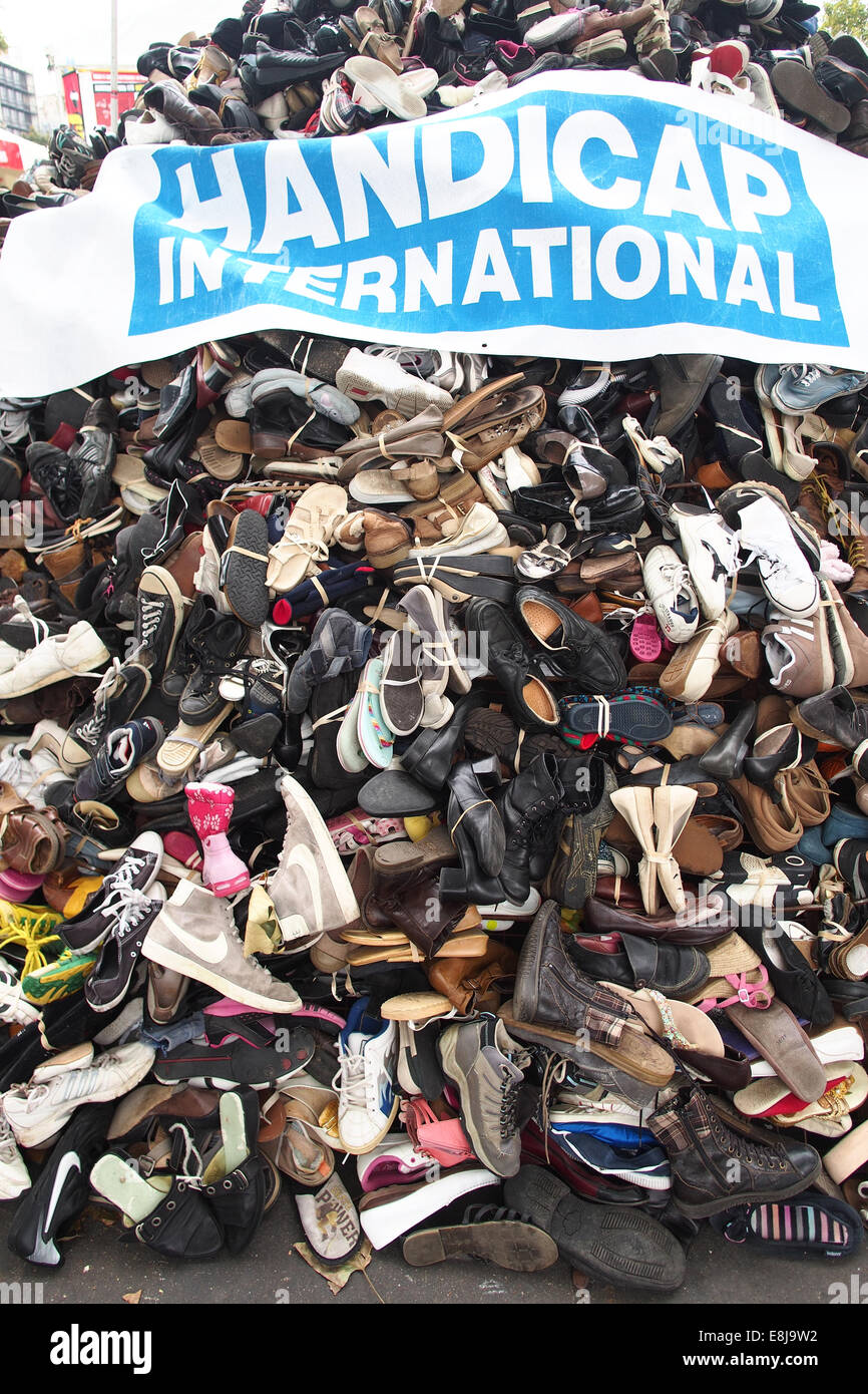 NGO Handicap International. Banner and shoes. Symbolization of landmines injuries. - Stock Image