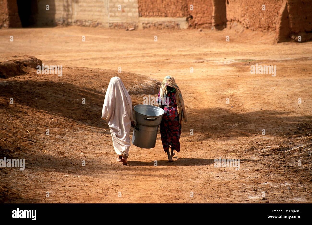 Tuareg population of Timimoun in Algeria. Two women walking home from the market. - Stock Image