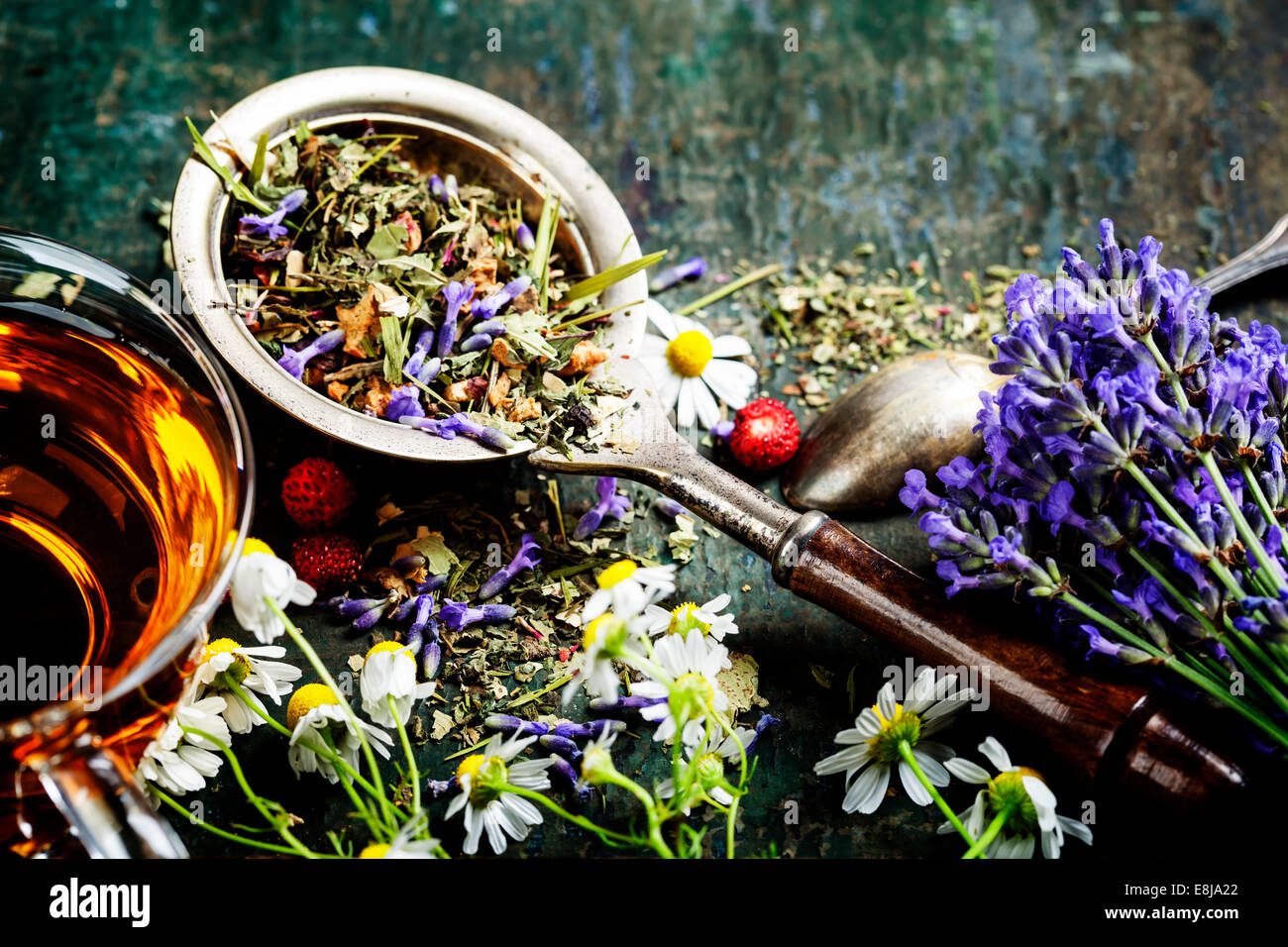 Herbal tea with wild flowers and berry on wooden background - bio food, health and diet concept - Stock Image