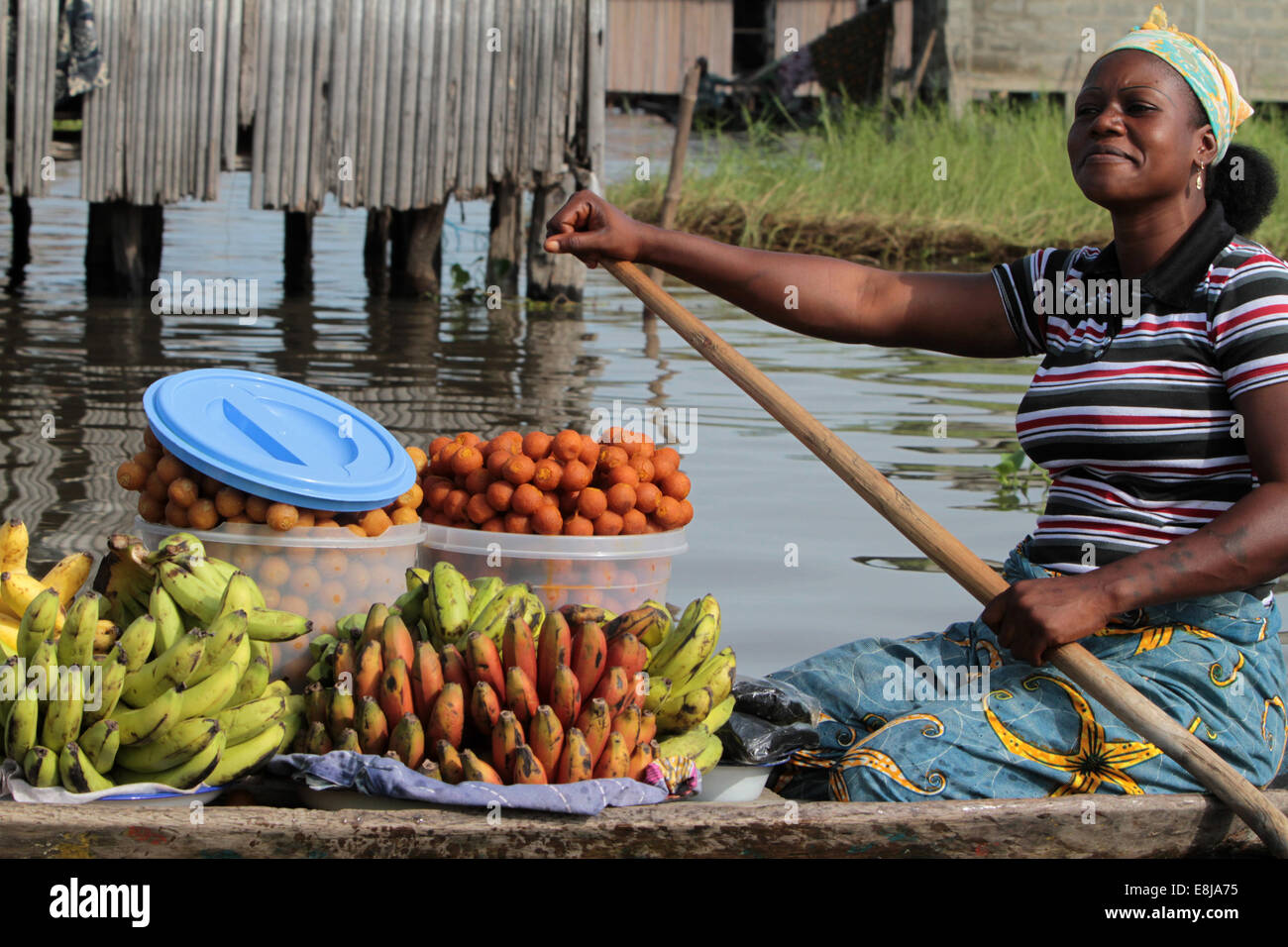 African woman market paddling a canoe carrying fruit. - Stock Image