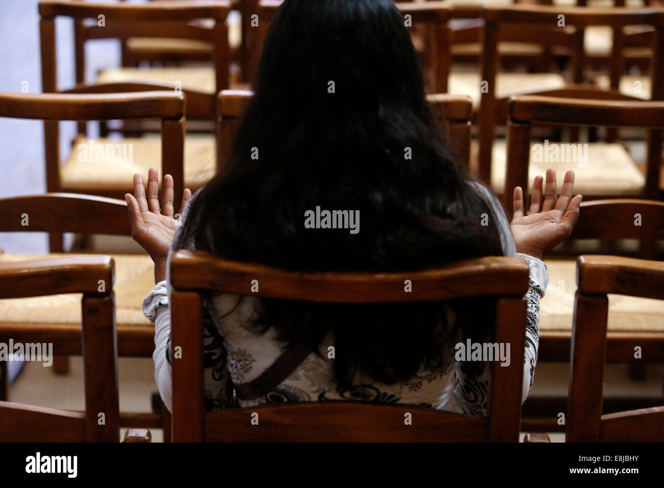 Basilica of St. Denis. Woman praying in the nave, turned towards the altar. - Stock Image