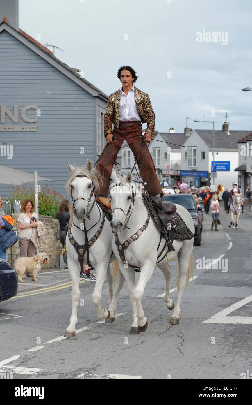 An equestrian riding two Lusitano dressage horses leads the opening procession of the Abersoch Jazz Festival 2014, - Stock Image
