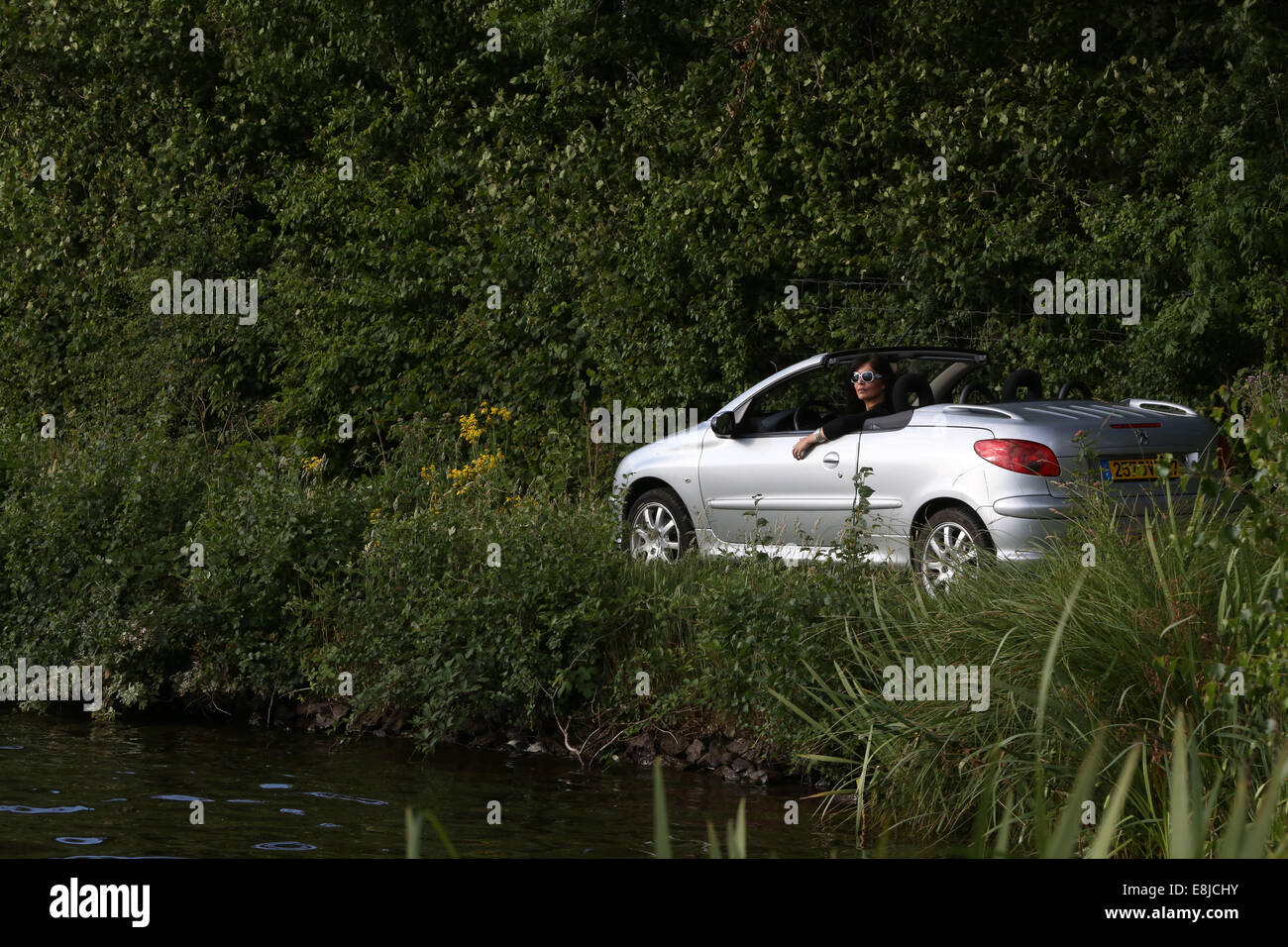 Driving a Peugeot 206 convertible. - Stock Image