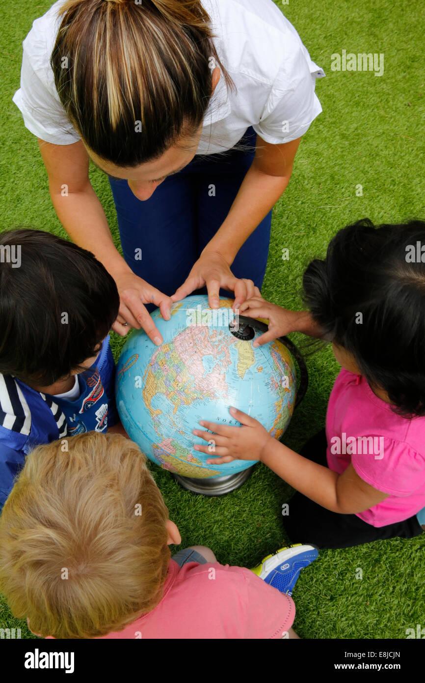 Kindergarten teacher showing countries on a globe - Stock Image