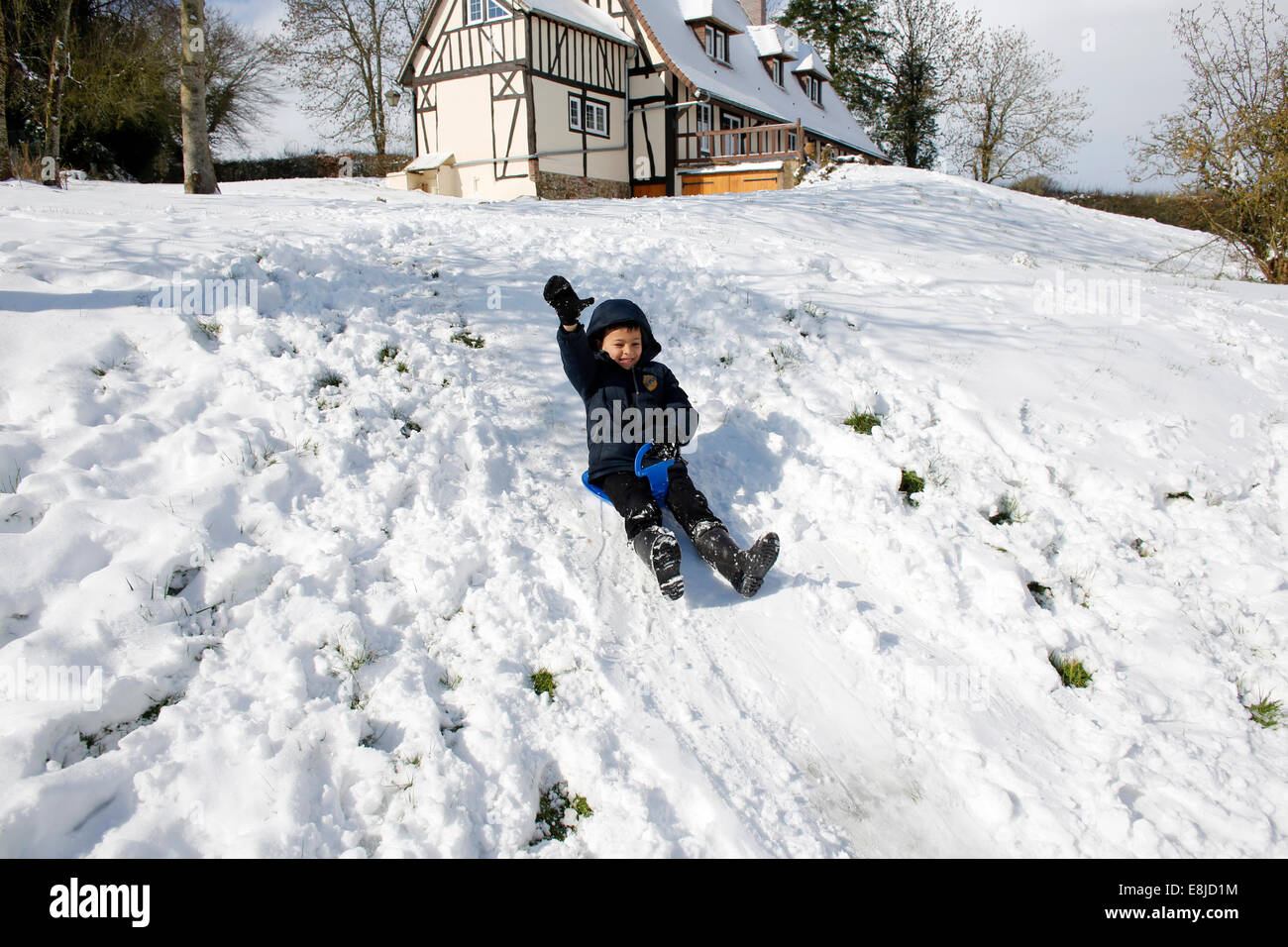 7-year-old boy sliding on a sleigh - Stock Image