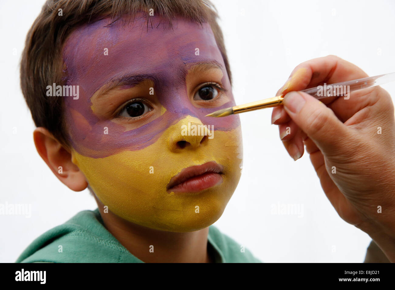 7-year-old boy having his face painted - Stock Image