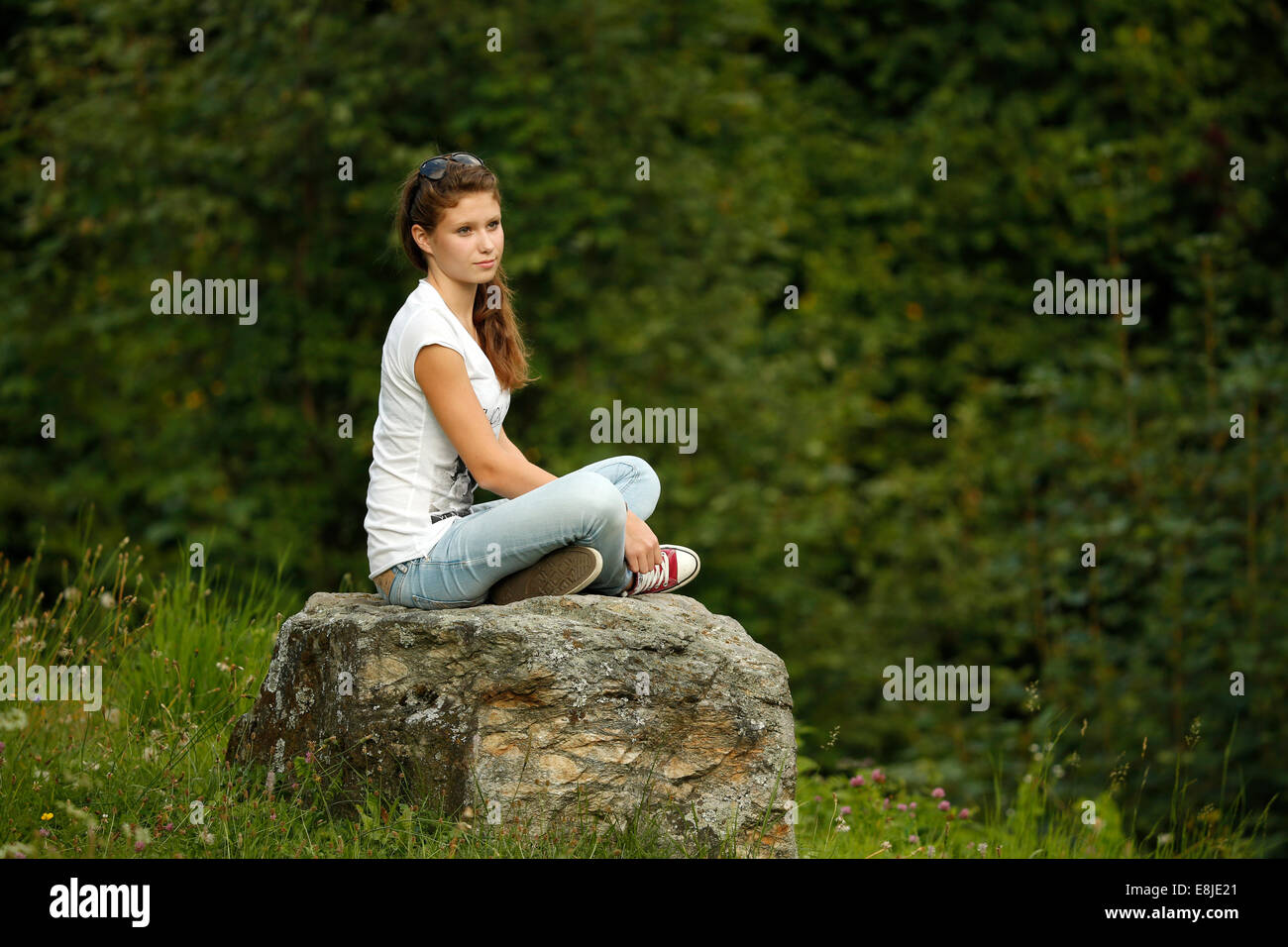 Young girl siting on a stone. - Stock Image
