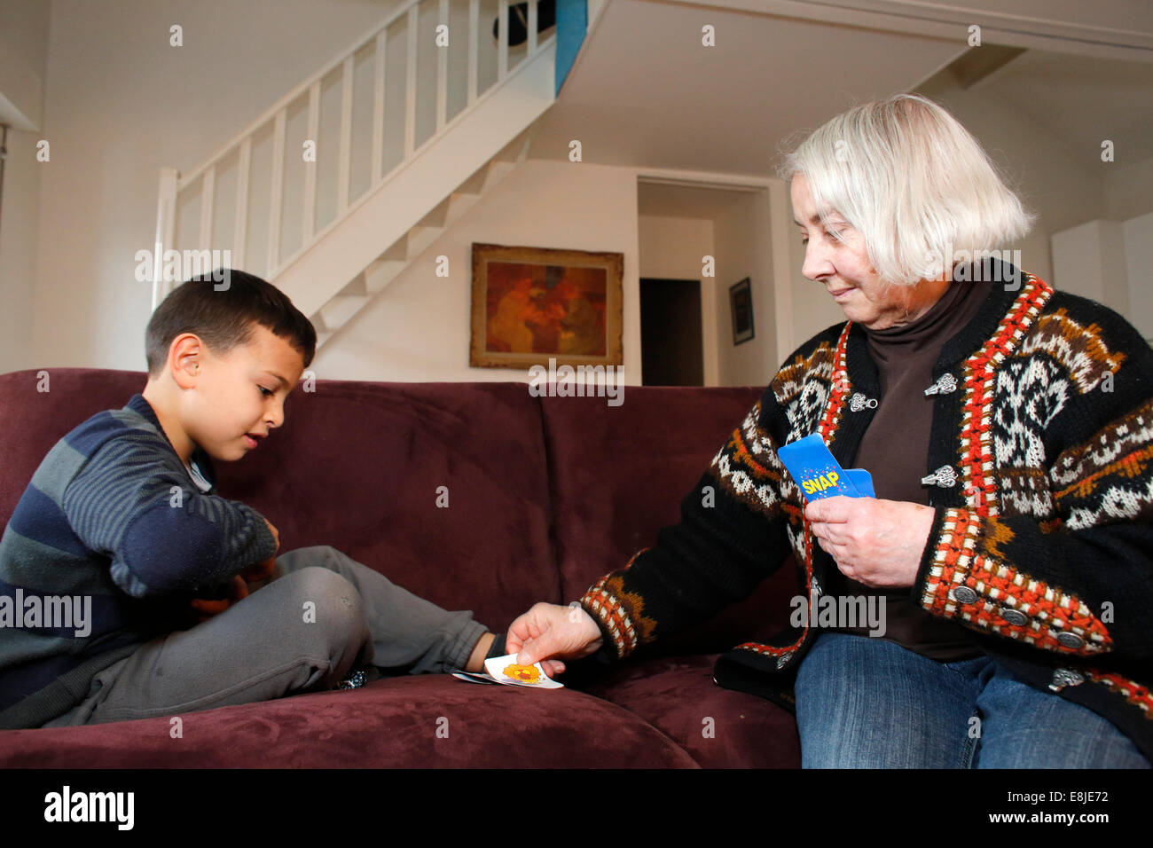 7-year-old boy playing cards with his grandmother - Stock Image