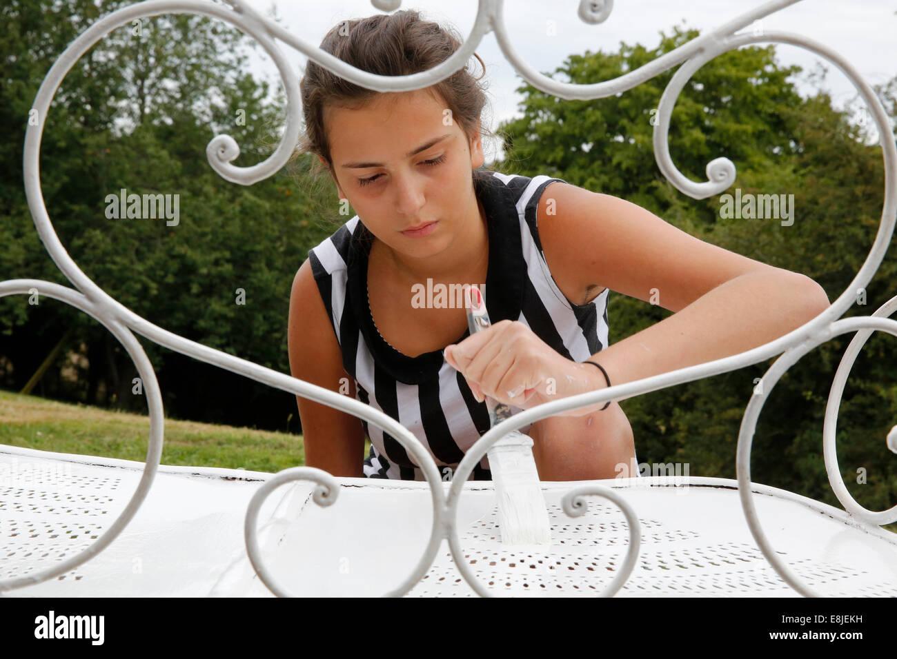 Teenager painting iron furniture - Stock Image