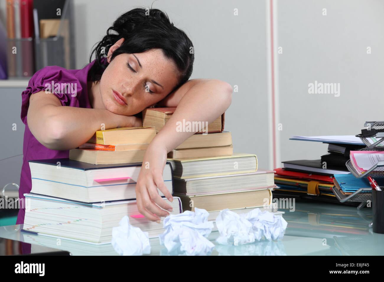 Woman sleeping on her books - Stock Image