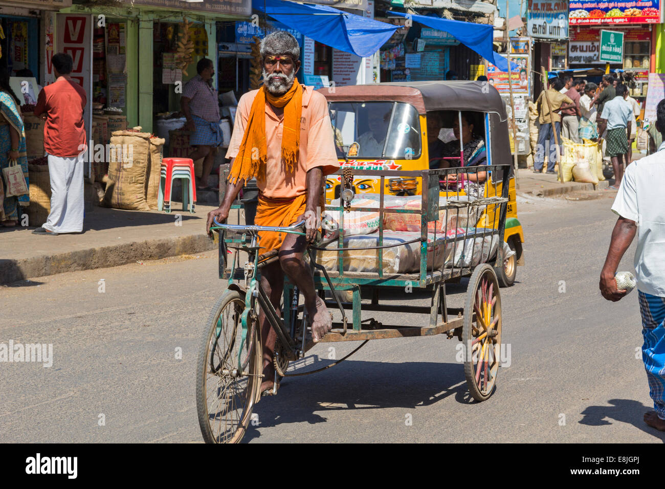 RICKSHAW DRIVER AND A LOAD OF HEAVY SACKS INDIA - Stock Image
