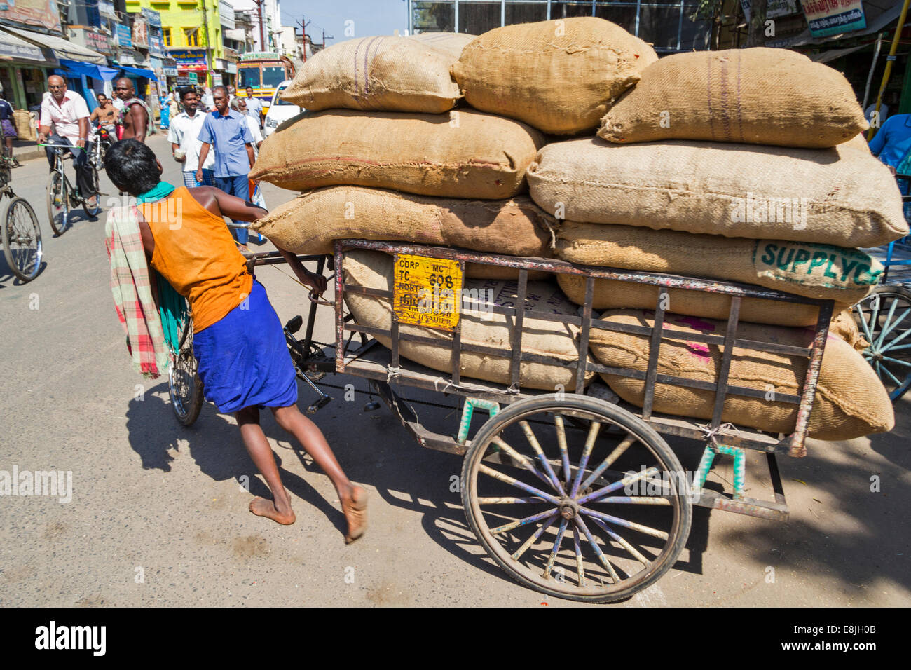 YOUNG RICKSHAW DRIVER AND A LOAD OF MANY HEAVY SACKS INDIA - Stock Image