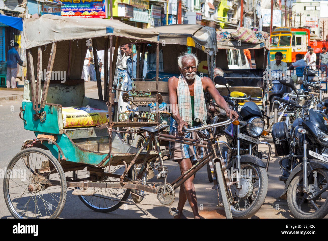 RICKSHAW DRIVER AND AN OLD RICKSHAW AMONG THE MODERN MACHINES IN THE STREETS OF INDIA - Stock Image