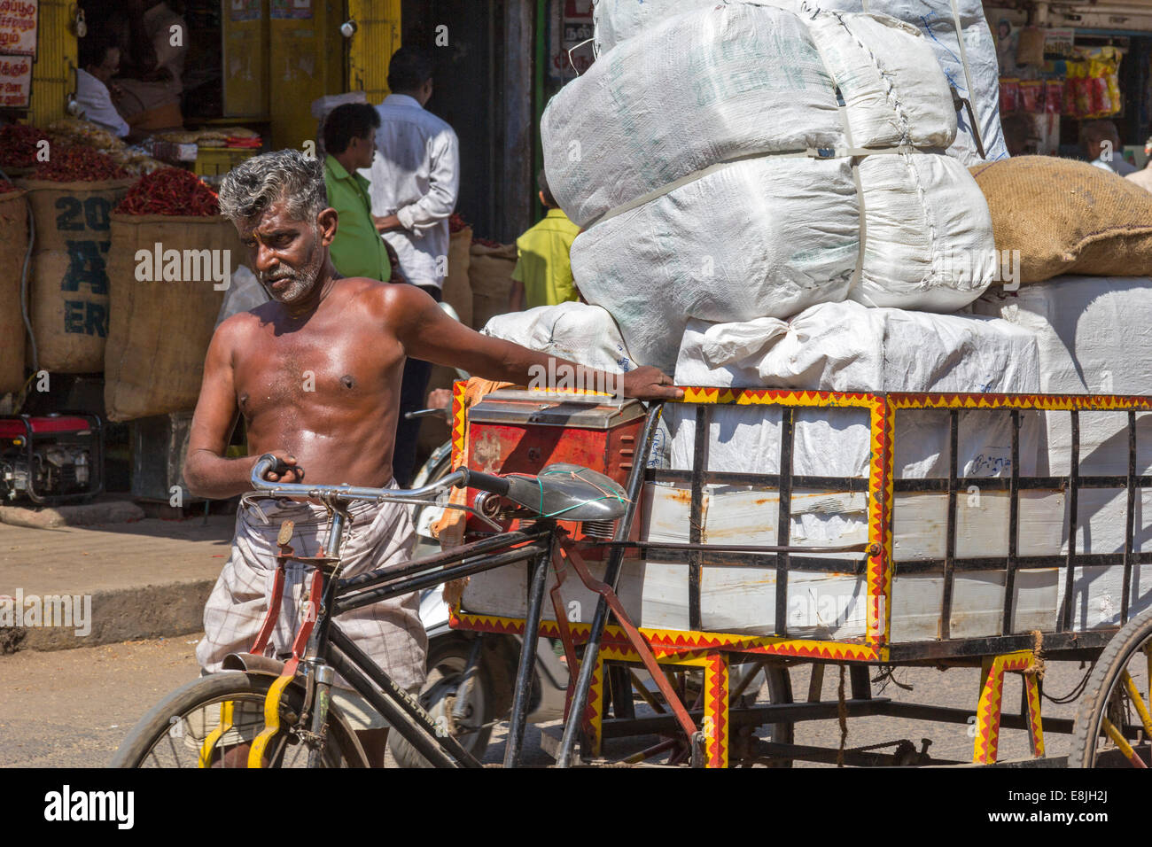 RICKSHAW DRIVER AND HIS BURDEN A VERY HEAVY LOAD INDIA - Stock Image