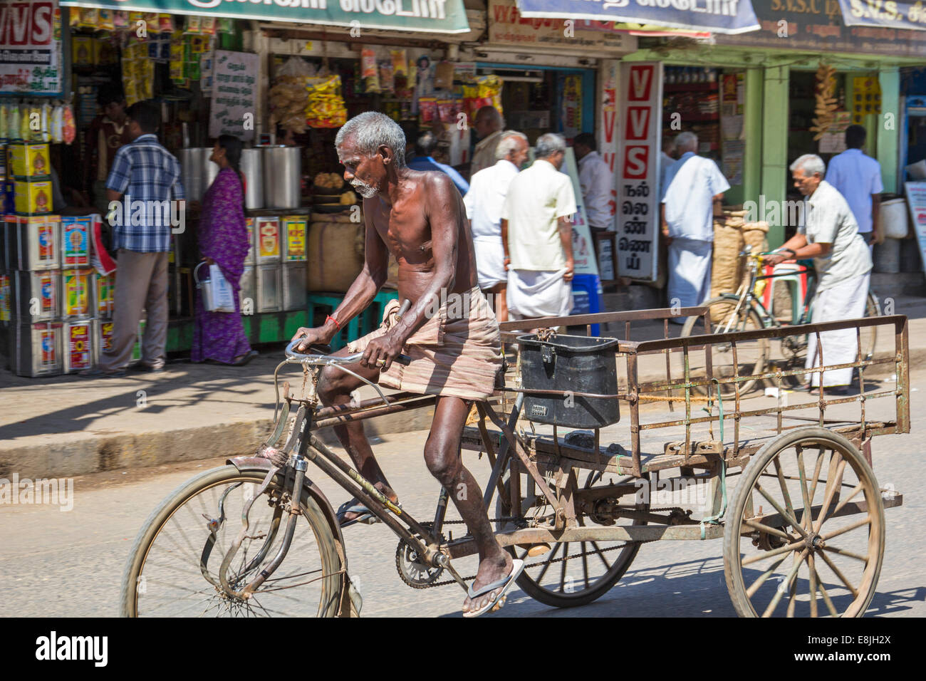OVERWORKED RICKSHAW DRIVER ON HIS WAY TO ANOTHER VERY HEAVY LOAD INDIA - Stock Image