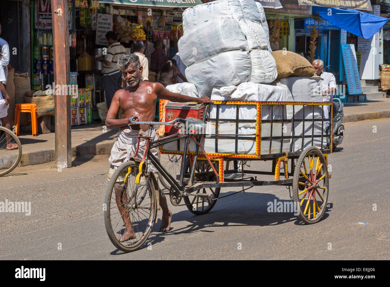 RICKSHAW DRIVER WALKING WITH A LOAD OF MANY HEAVY SACKS IN INDIA - Stock Image