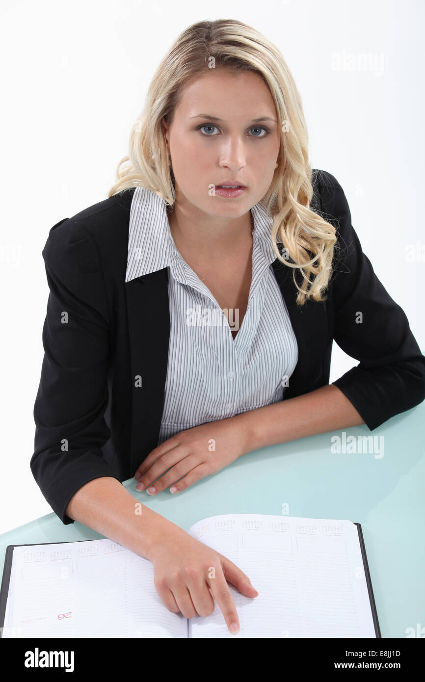 Blond woman checking diary for free appointments Stock Photo
