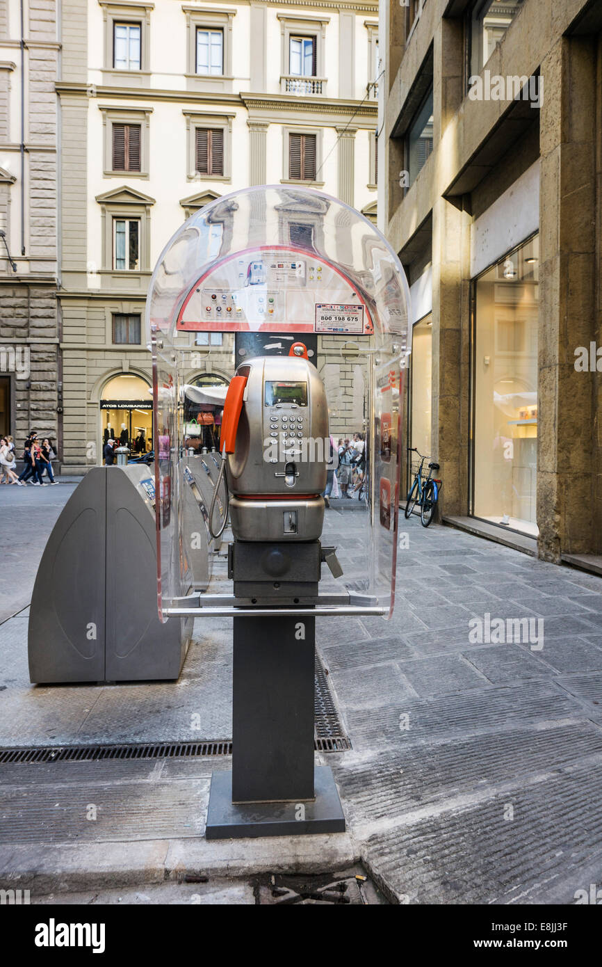 stylish transparent lucite public telephone kiosk & row of recycling containers in a small piazza Florence Firenze Stock Photo