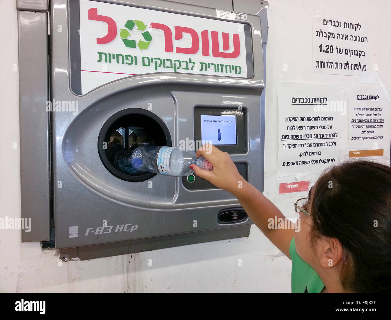 Bottle recycling. Young girl recycles bottles in an automatic machine. Photographed in Israel - Stock Image