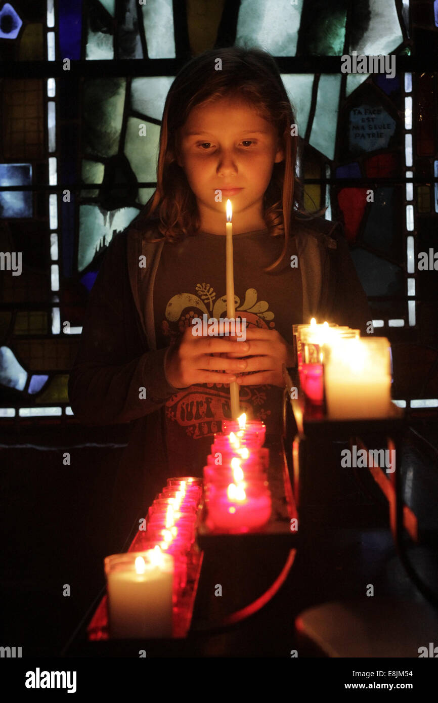 Girl holding a candle in a church. - Stock Image