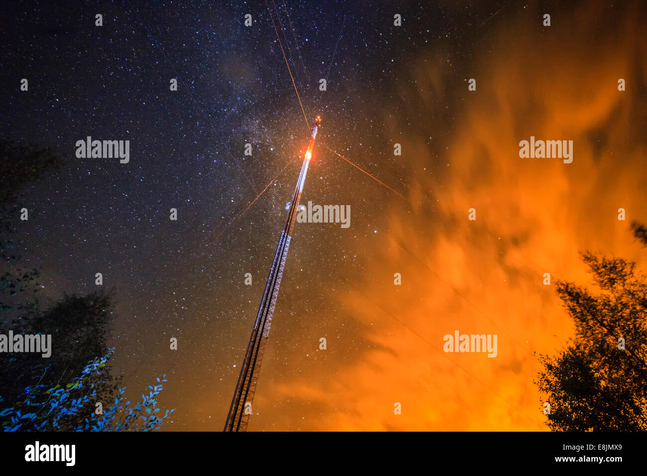 A telecommunication link tower with a blinking light. Night sky with stars on the background. - Stock Image