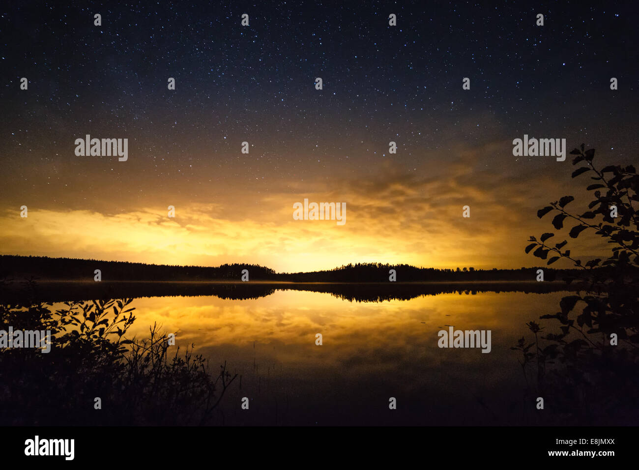 Stars over the sunset scene in Finland. Reflections of the forest skyline in the calm water of a lake. - Stock Image