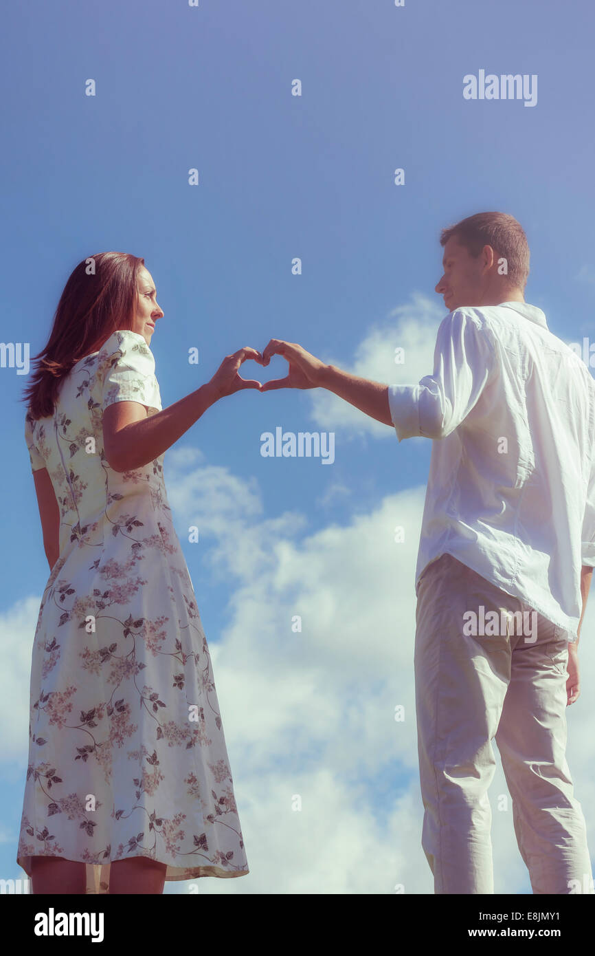 a couple forming a heart with their hands - Stock Image