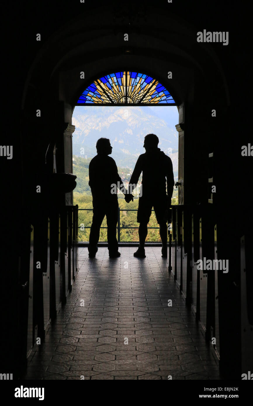 Silhouette of a gay couple to the output of church. - Stock Image