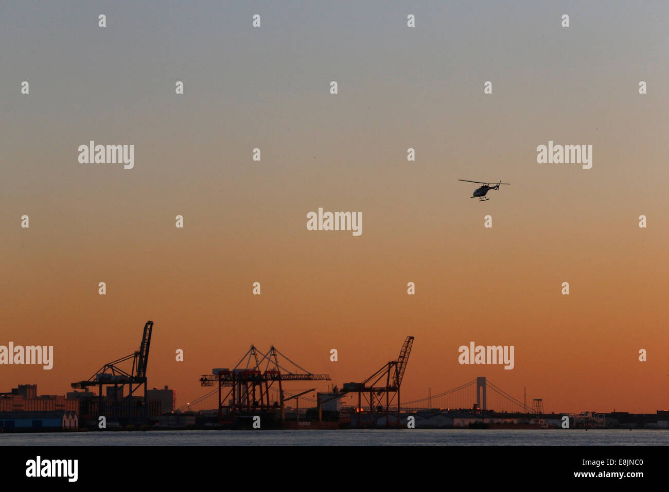 Helicopter and container cranes at sunset. - Stock Image